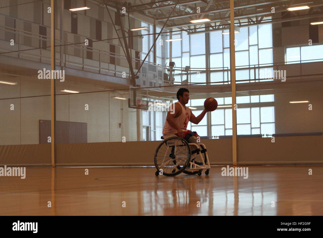 Sgt. Eric Rodriguez, a native of San Diego, California, dribbles down the court during wheelchair basketball practice - Stock Image