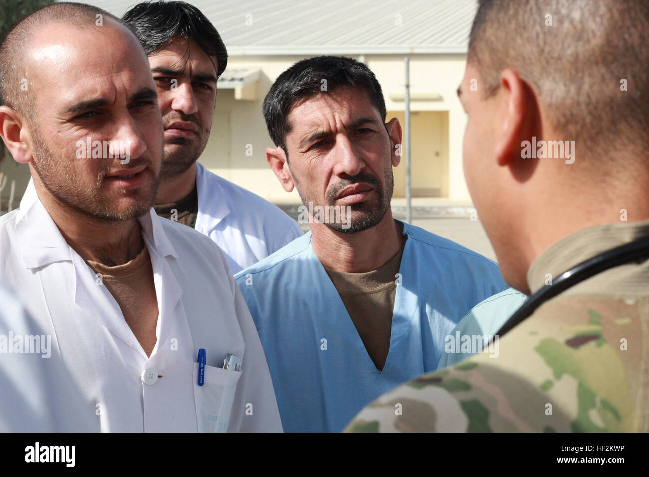 Three medical personnel from the Air Transport Trauma Unit of the Afghan National Army's 205th Corps, receive instruction - Stock Image