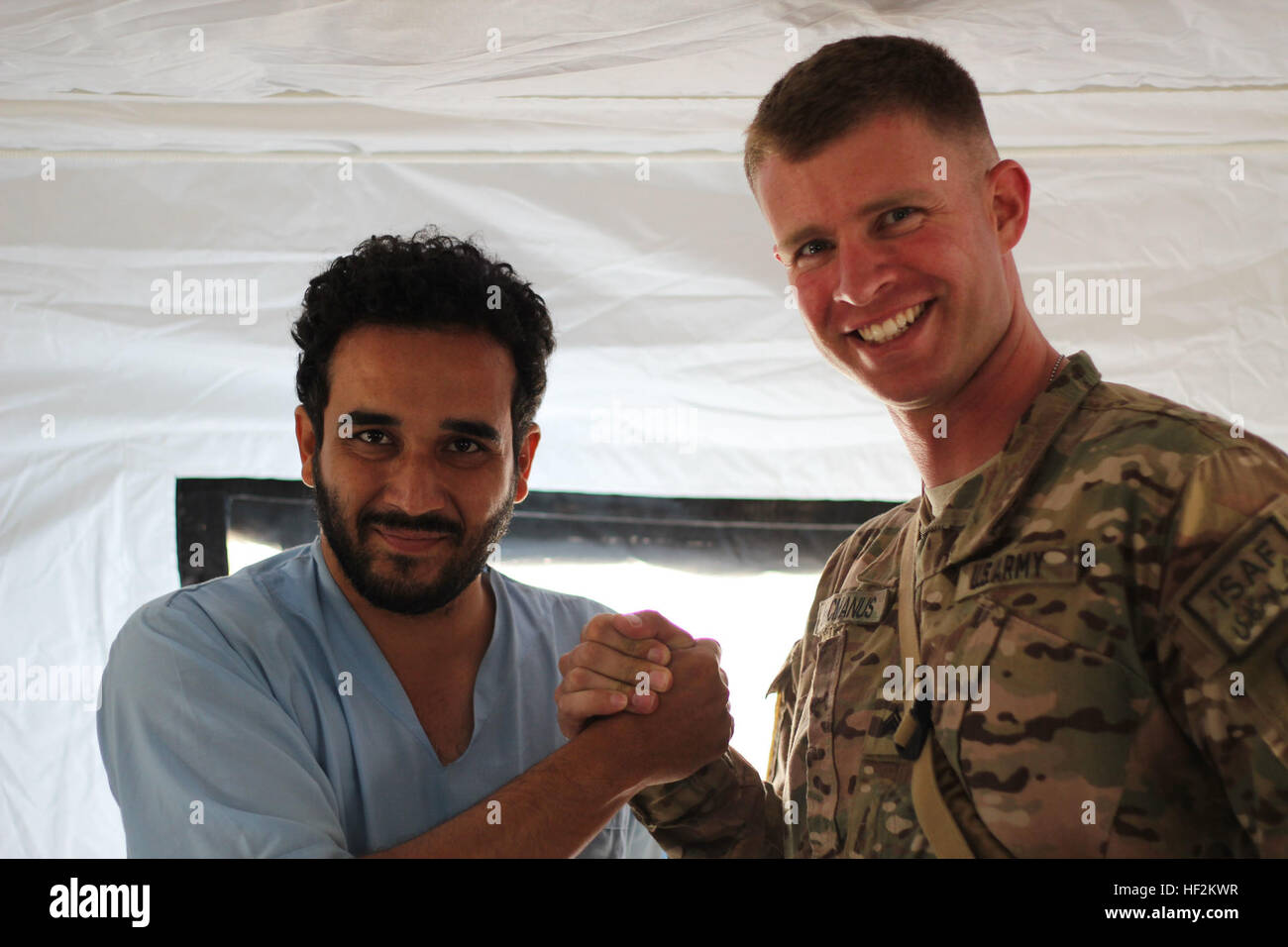 Sgt. Raymond Macmanus (right) of the 250th Forward Surgical Team, 62nd Medical Brigade, shakes hands with an Afghan - Stock Image