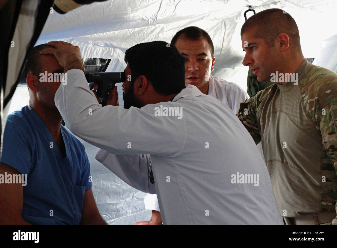 Maj. Justin Mitchell (far right) serving with the 250th Forward Surgical Team, 62nd Medical Brigade, gives medical - Stock Image