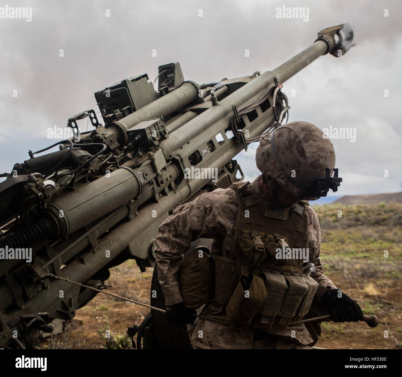 Cpl. Calvin V. Montgomery uses his whole body to pull the lanyard of an M777 Howitzer, firing a 155 mm round March Stock Photo