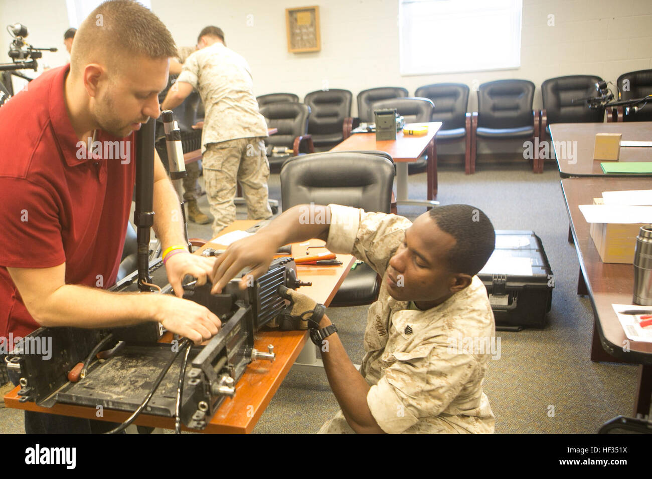Mr. Daniel Swick, a civilian contractor, helps Sgt. Kharlange Joseph, an explosive ordnance disposal technician - Stock Image
