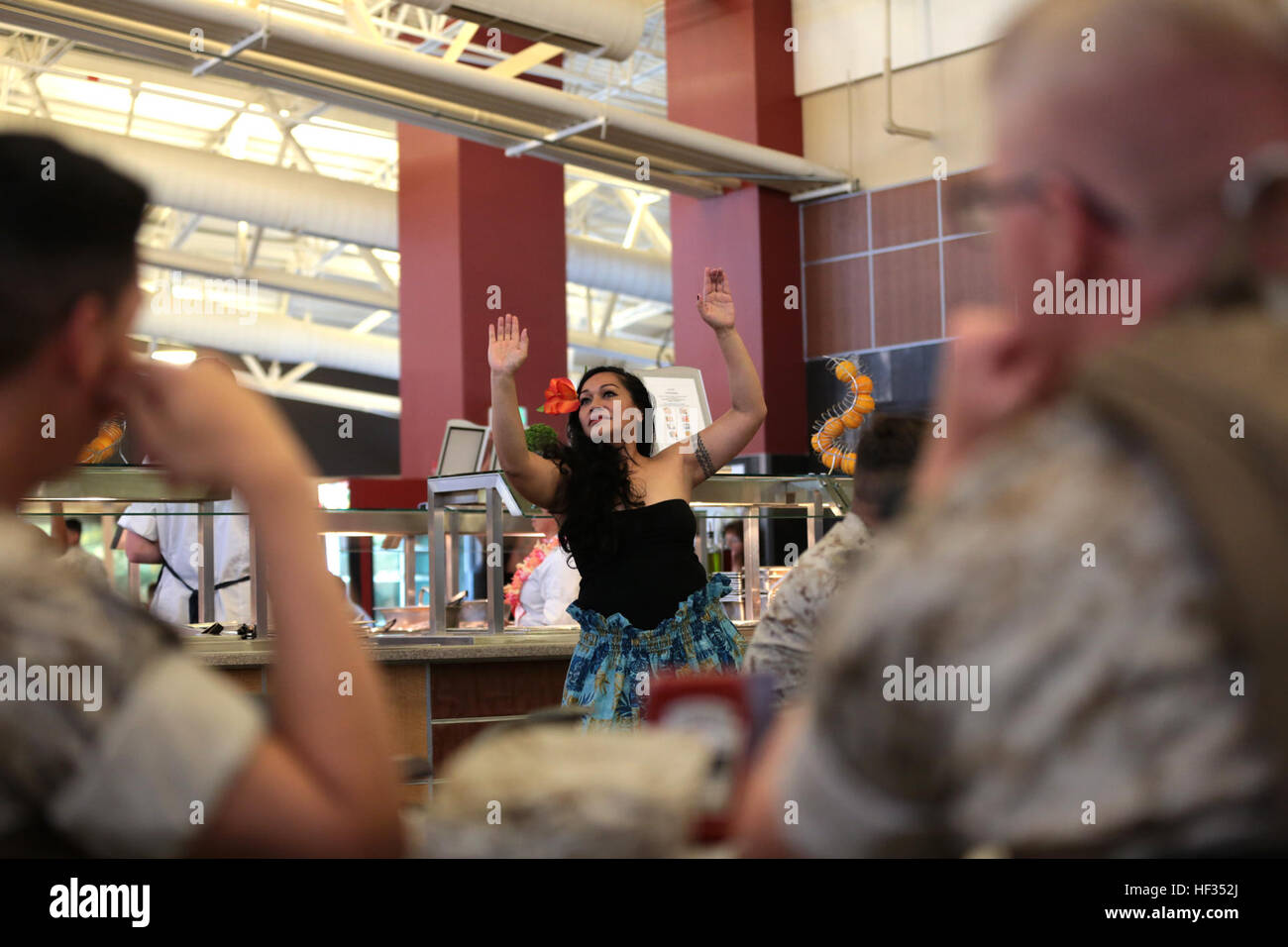 Joyce Te'o, volunteer dancer, hula dances to traditional Hawaiian music at Littleton Dining Facility aboard the - Stock Image