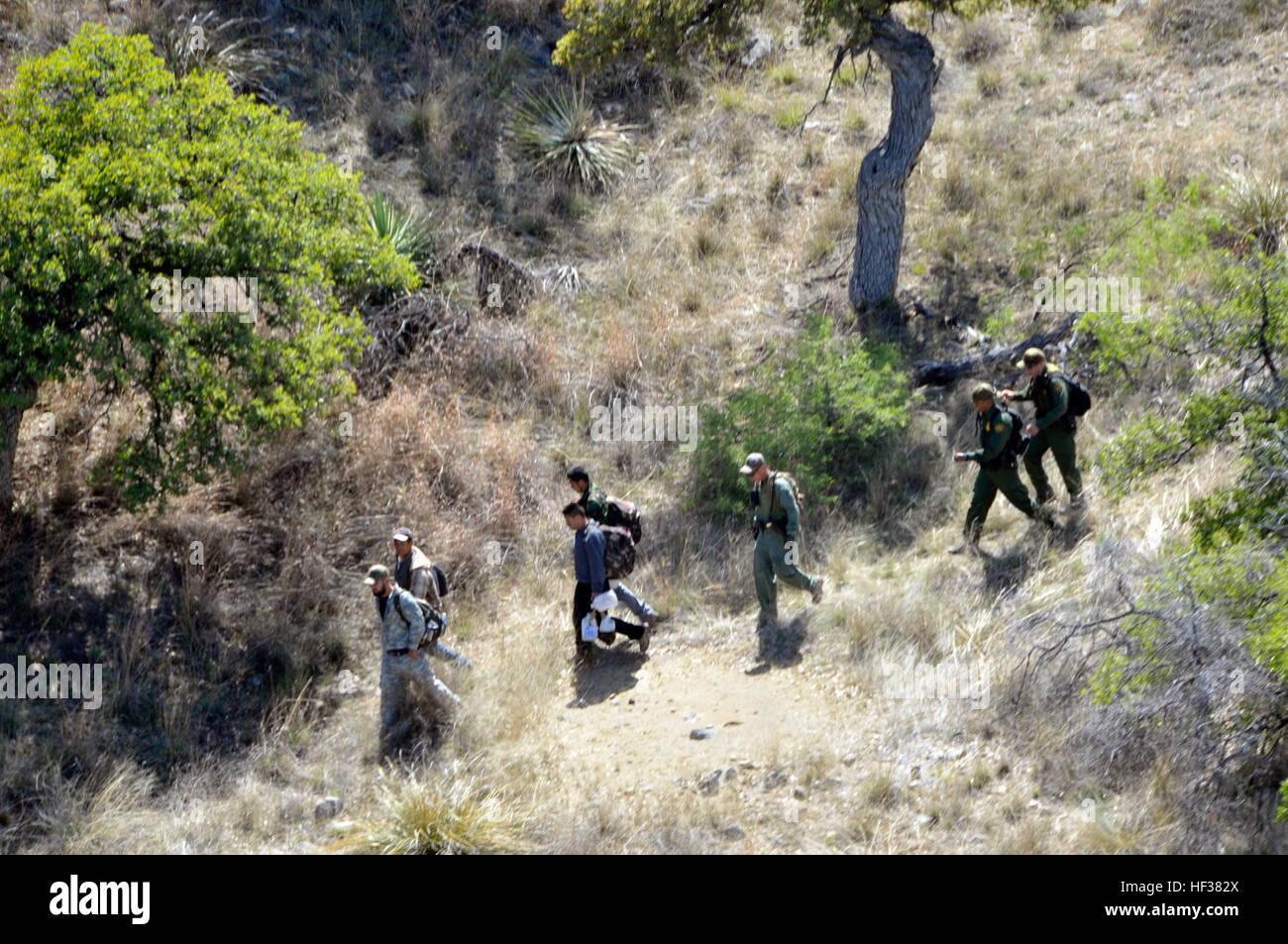 U.S. Border Patrol agents escort four undocumented immigrants captured near the U.S.-Mexico border on April 23, - Stock Image