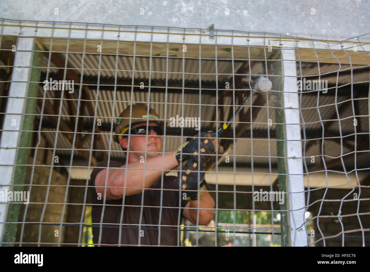 KIRABATI (June 3, 2015) – Steelworker 3rd Class Jonathon Walsh removes wire as part of a construction project to - Stock Image