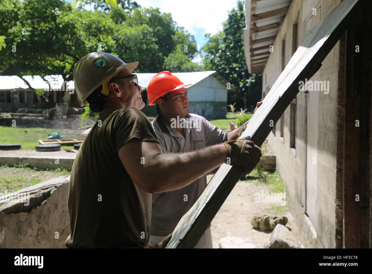 KIRABATI (June 3, 2015) – Steelworker 3rd Class Johnathon Walsh, left, assists a local construction worker in removing Stock Photo