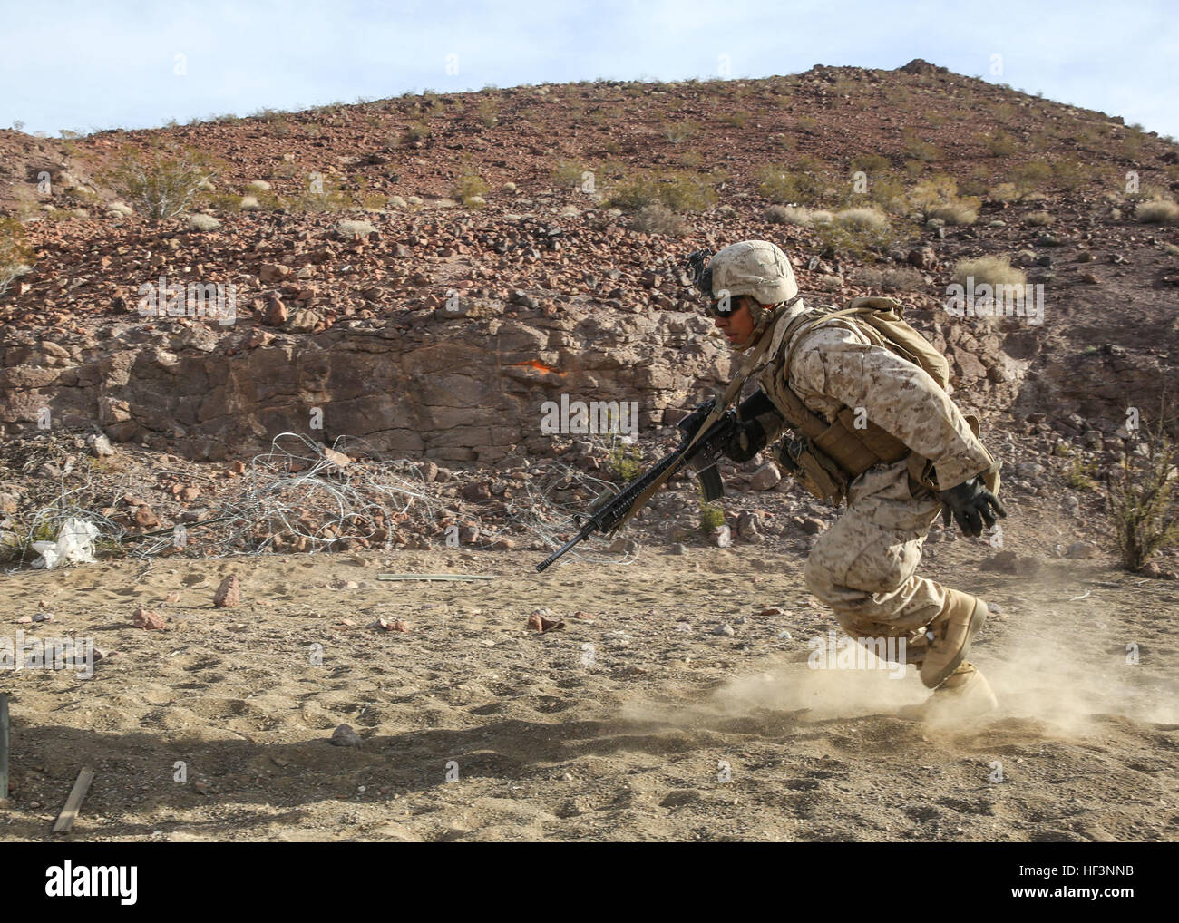 A Marine darts for cover during a company supported, live-fire assault during a Marine Corps Combat Readiness Evaluation - Stock Image