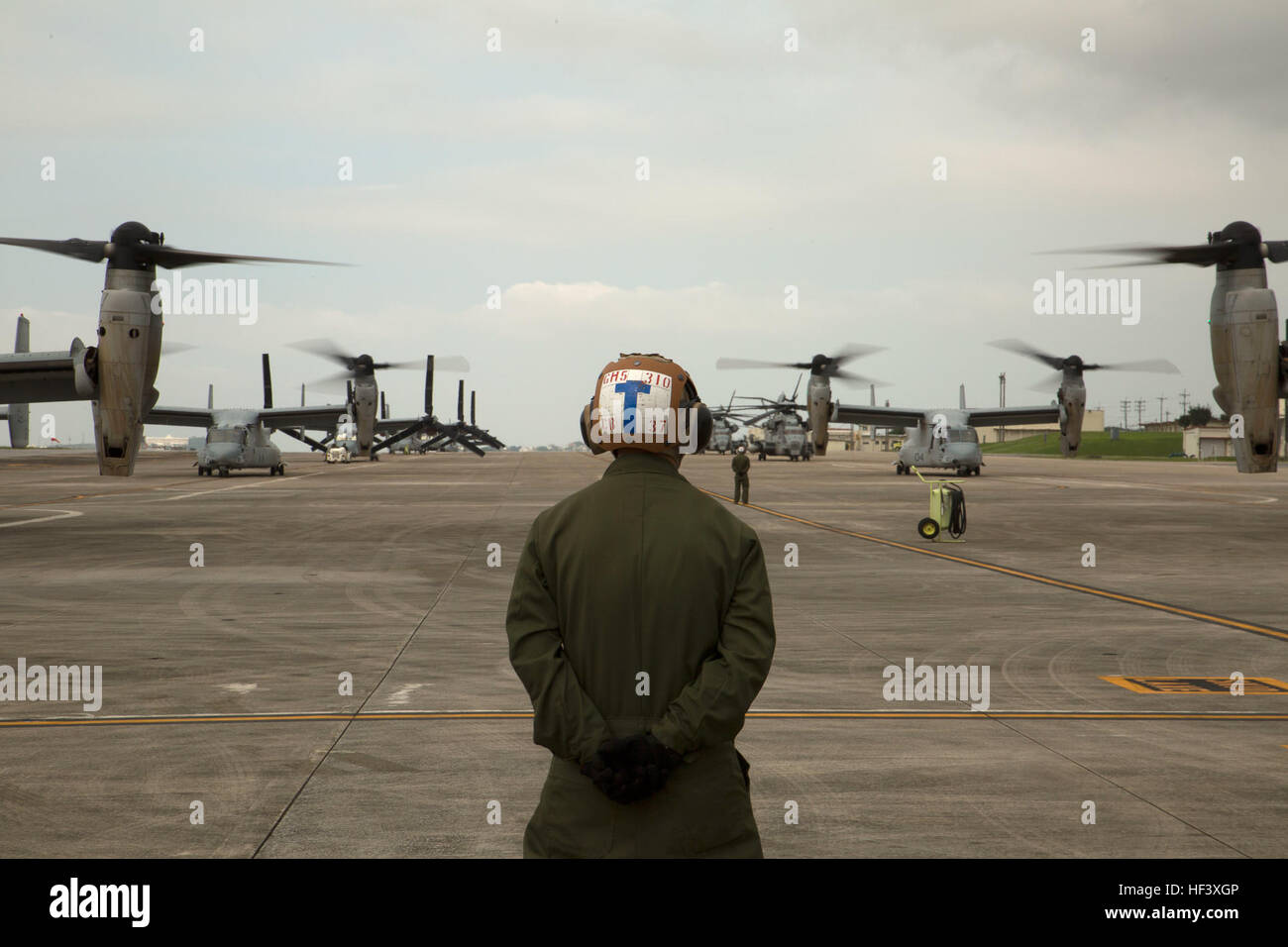 A Marine waits to guide MV-22 Ospreys with Marine Medium Tiltrotor Squadron 265, 31st Marine Expeditionary Unit, Stock Photo