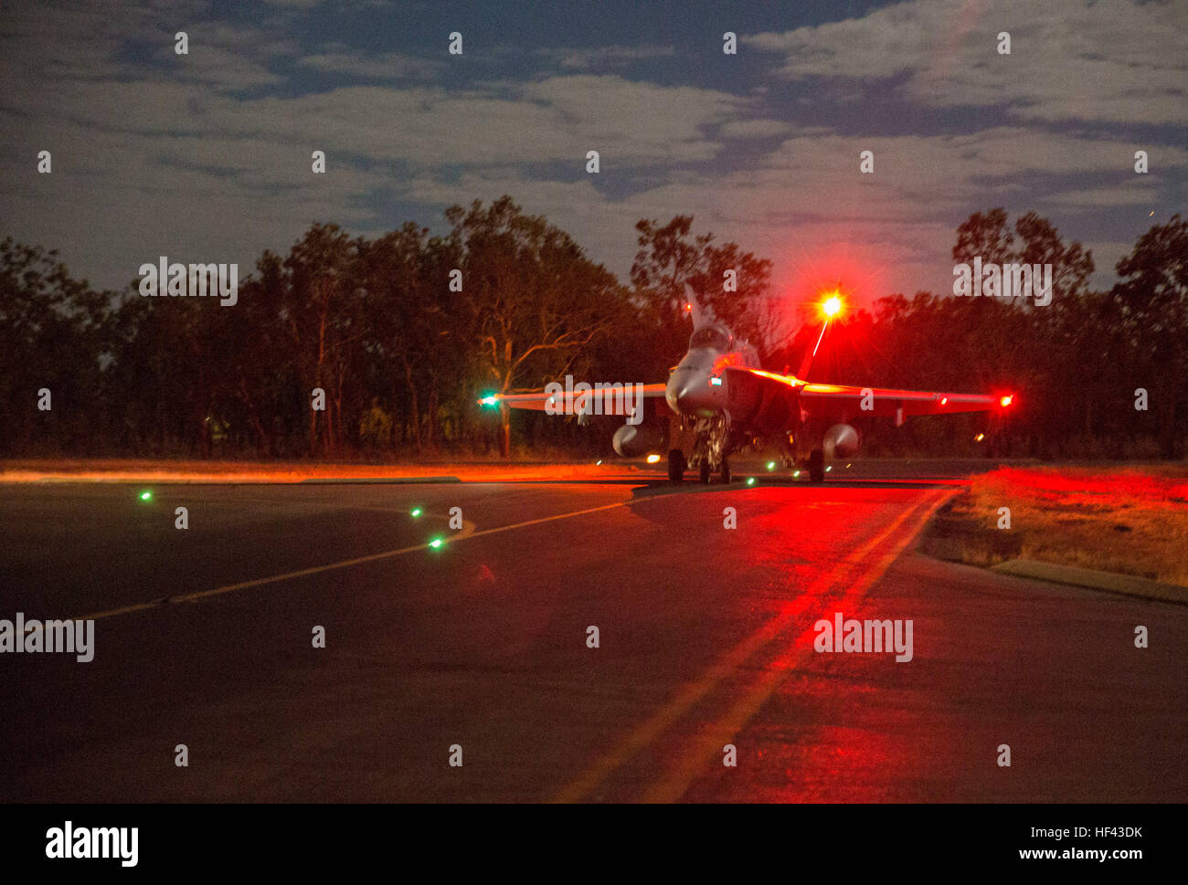 An F/A-18C Hornet assigned to Marine Fighter Attack Squadron (VMFA) 122 taxis to the runway for a night flight during - Stock Image