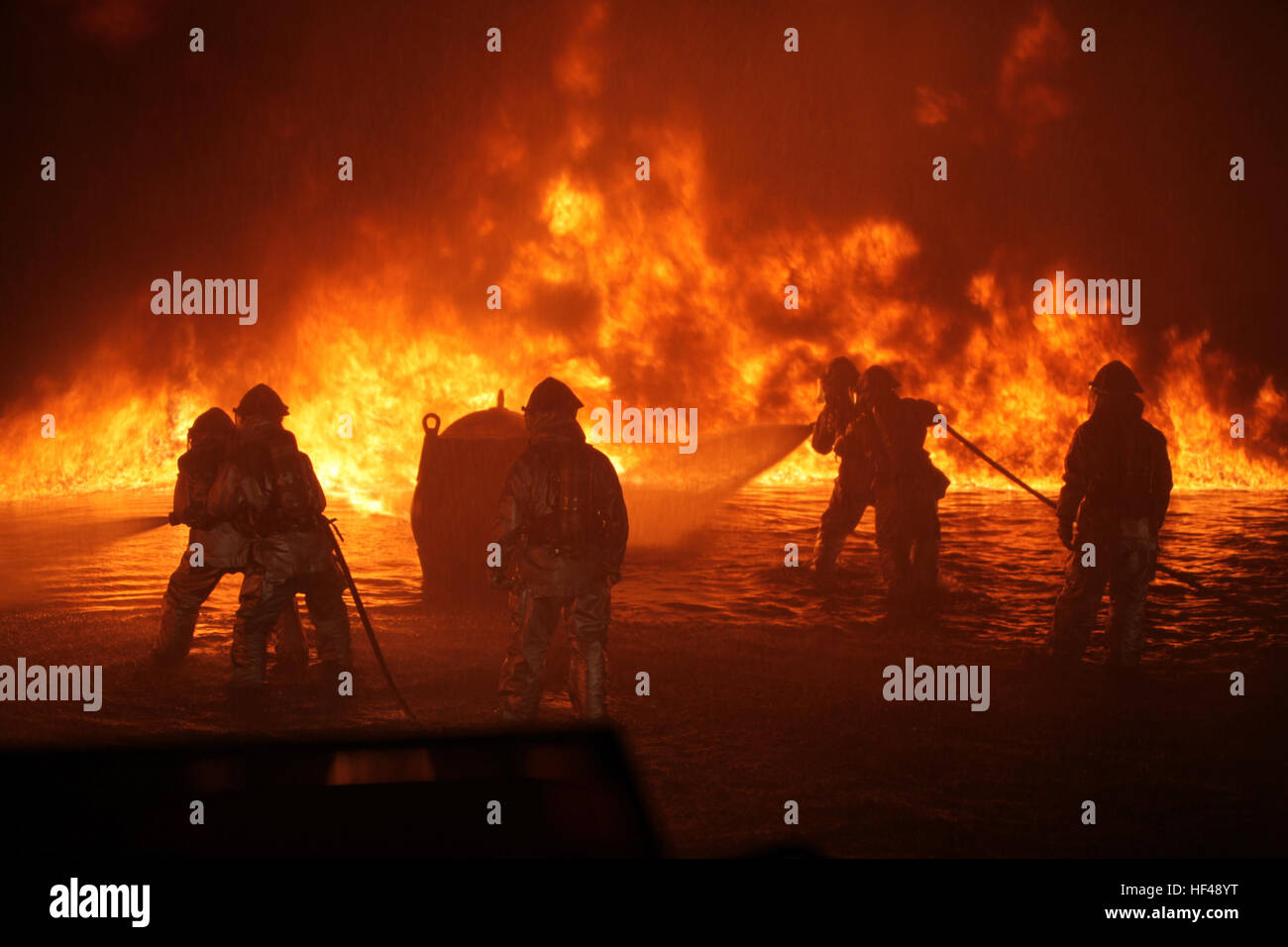 ARFF Marines start spraying the approaching fuel fire during a night fire training exercise at the fuel fire pit, - Stock Image