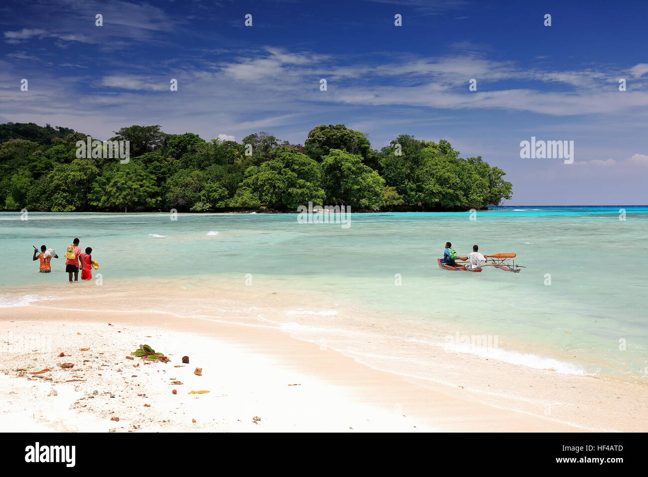 Port Olry, Vanuatu-October 19, 2014: Ni-Vanuatu boys cross by foot and boat at low tide the channel over the sand - Stock Image