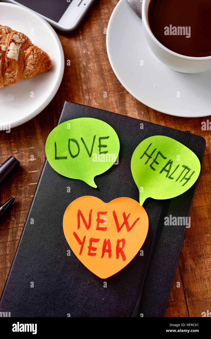 a sticky note with the text new year and two more sticky notes with the words love and health as wishes for the - Stock Image