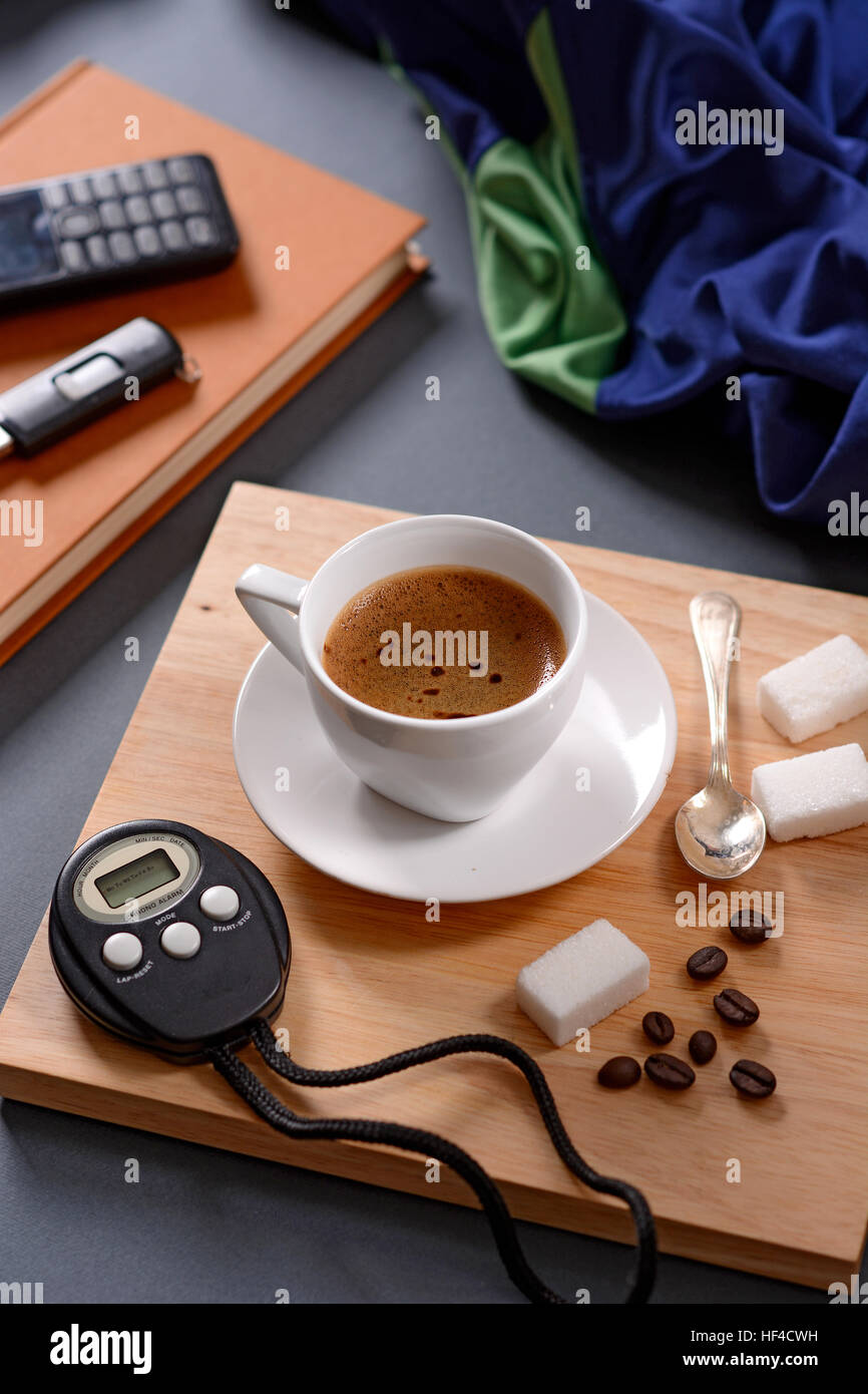 cup of coffee and chronograph on wooden tray - Stock Image