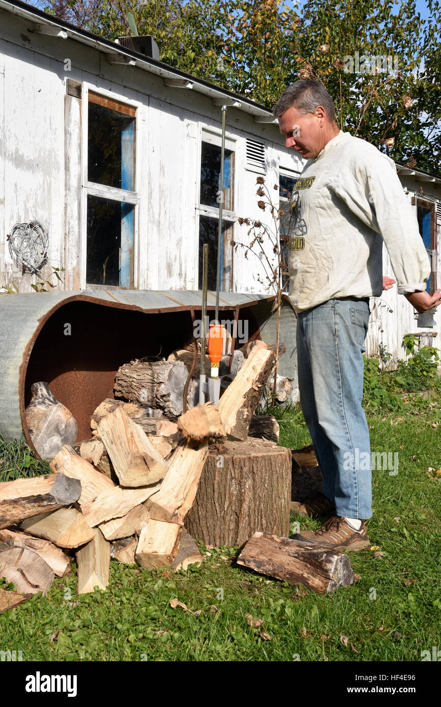 Splitting wood with a Smart Splitter on a farm or rural homestead. - Stock Image