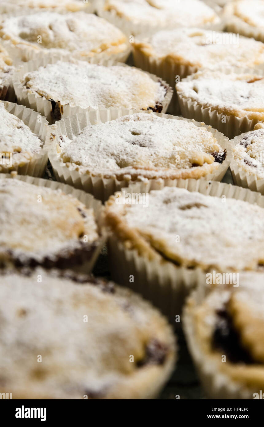 Homemade mince pies on a cooling rack. - Stock Image