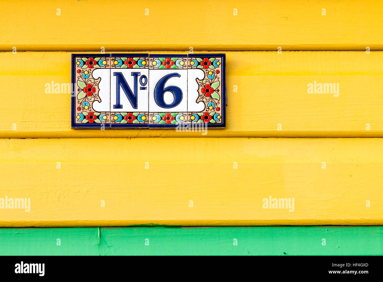 England, Whitstable. Number 6 plate with flower border on four tiles stuck on painted yellow boards, with green - Stock Image