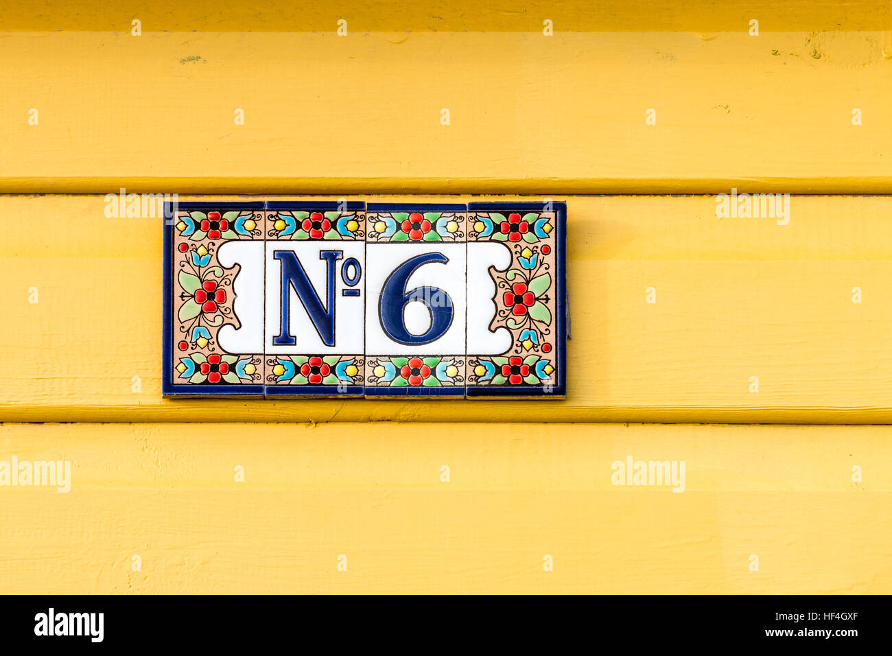 England, Whitstable. Number 6 plate with flower border on four tiles stuck on painted yellow boards. - Stock Image