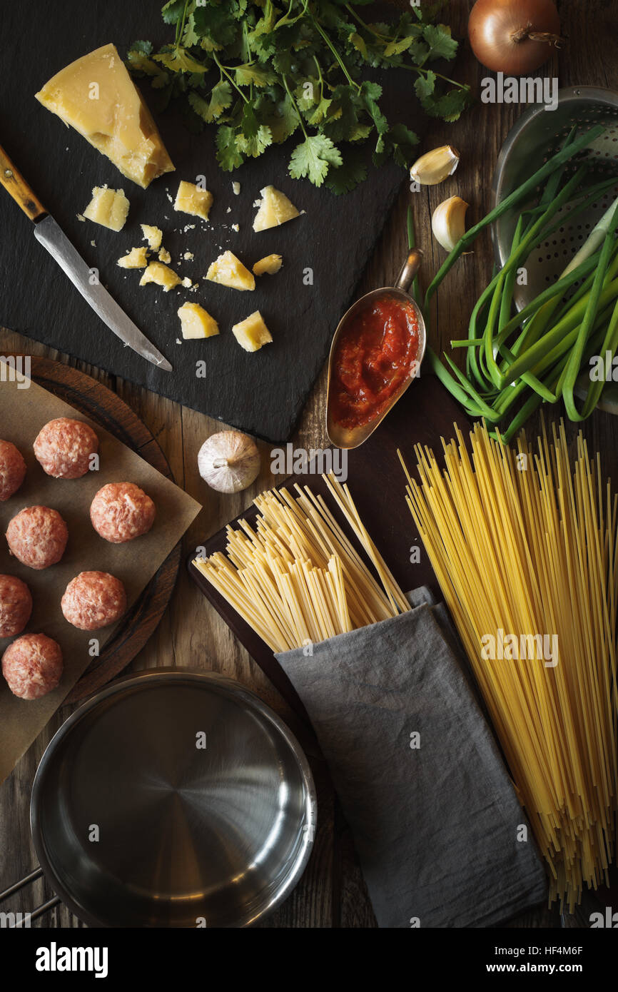 Ingredients for cooking spaghetti, meatballs with cheese and fresh herbs vertical top view - Stock Image