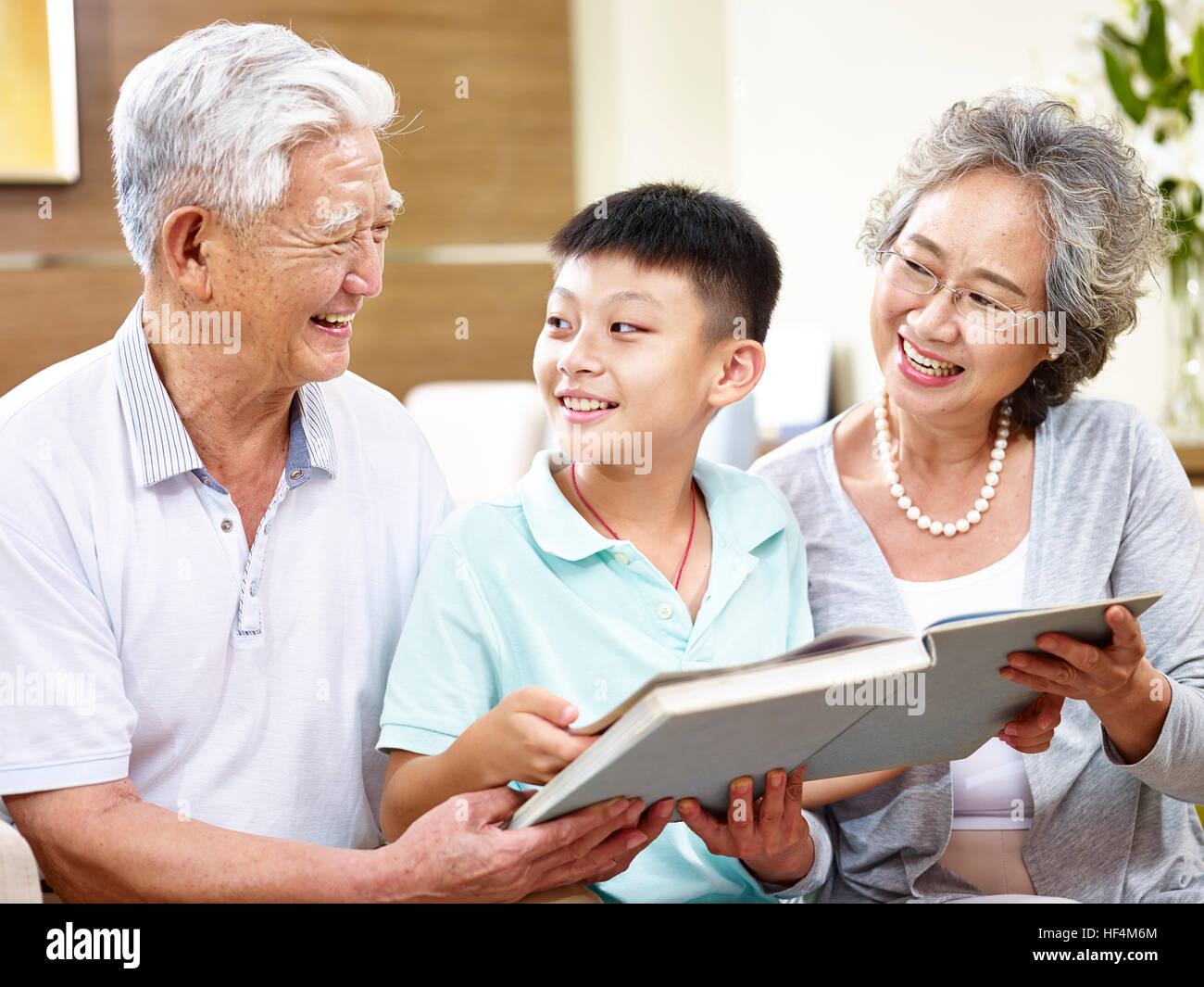 happy asian grandfather and grandmother reading a book with grandson