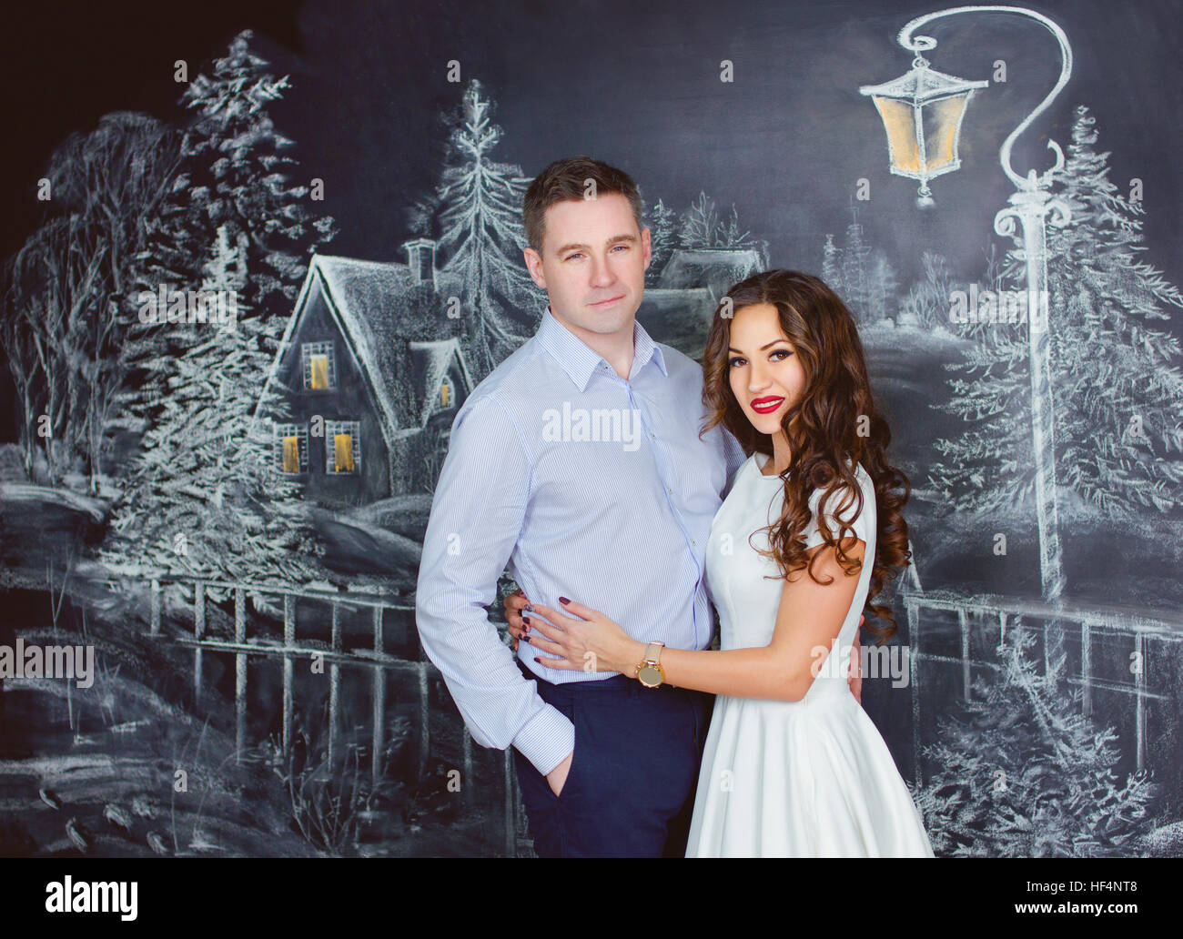 young beautiful caucasian woman and man on background of drawing winter street - Stock Image