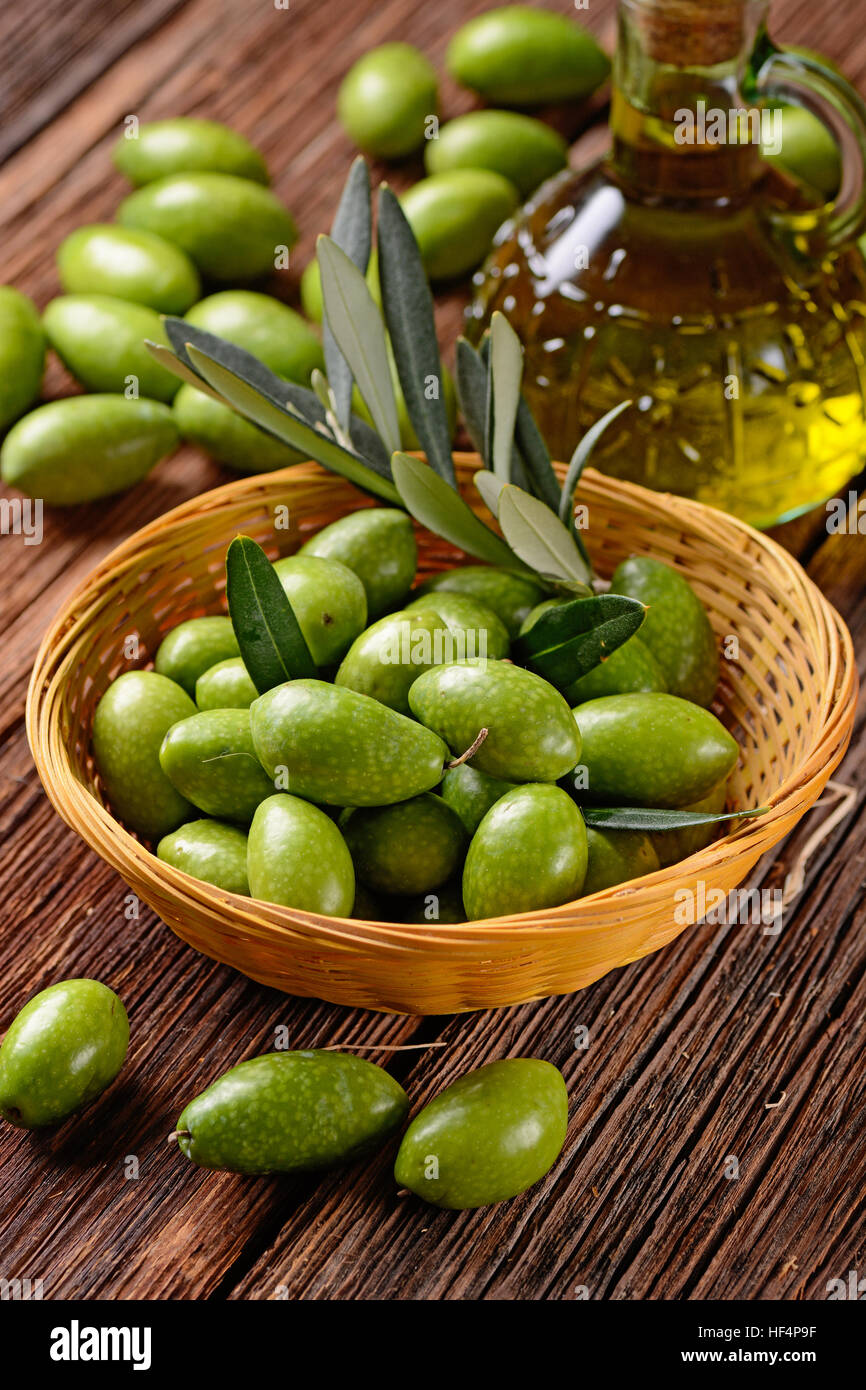 fresh green olives on the wooden table - Stock Image
