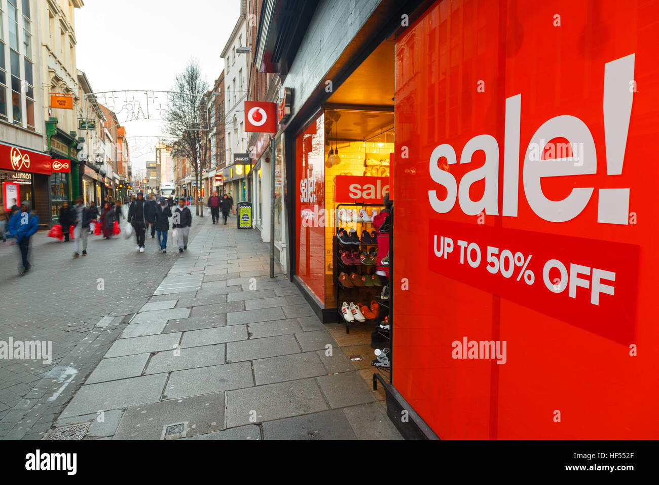 Big red Boxing Day sales poster and shoppers on Clumber Street in Nottingham. In Nottingham, England. - Stock Image