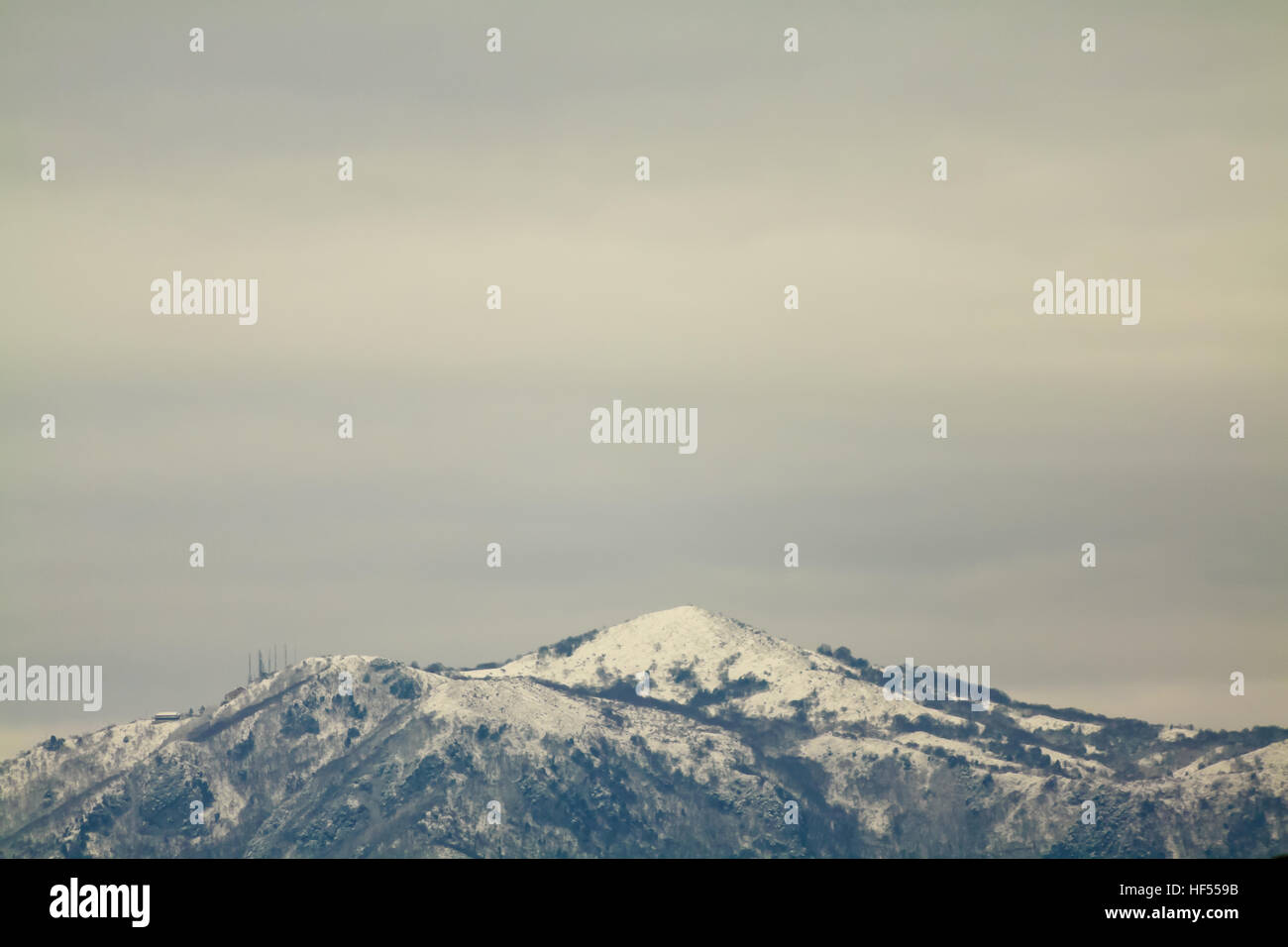 Snowy mountain top with dark sky - Stock Image