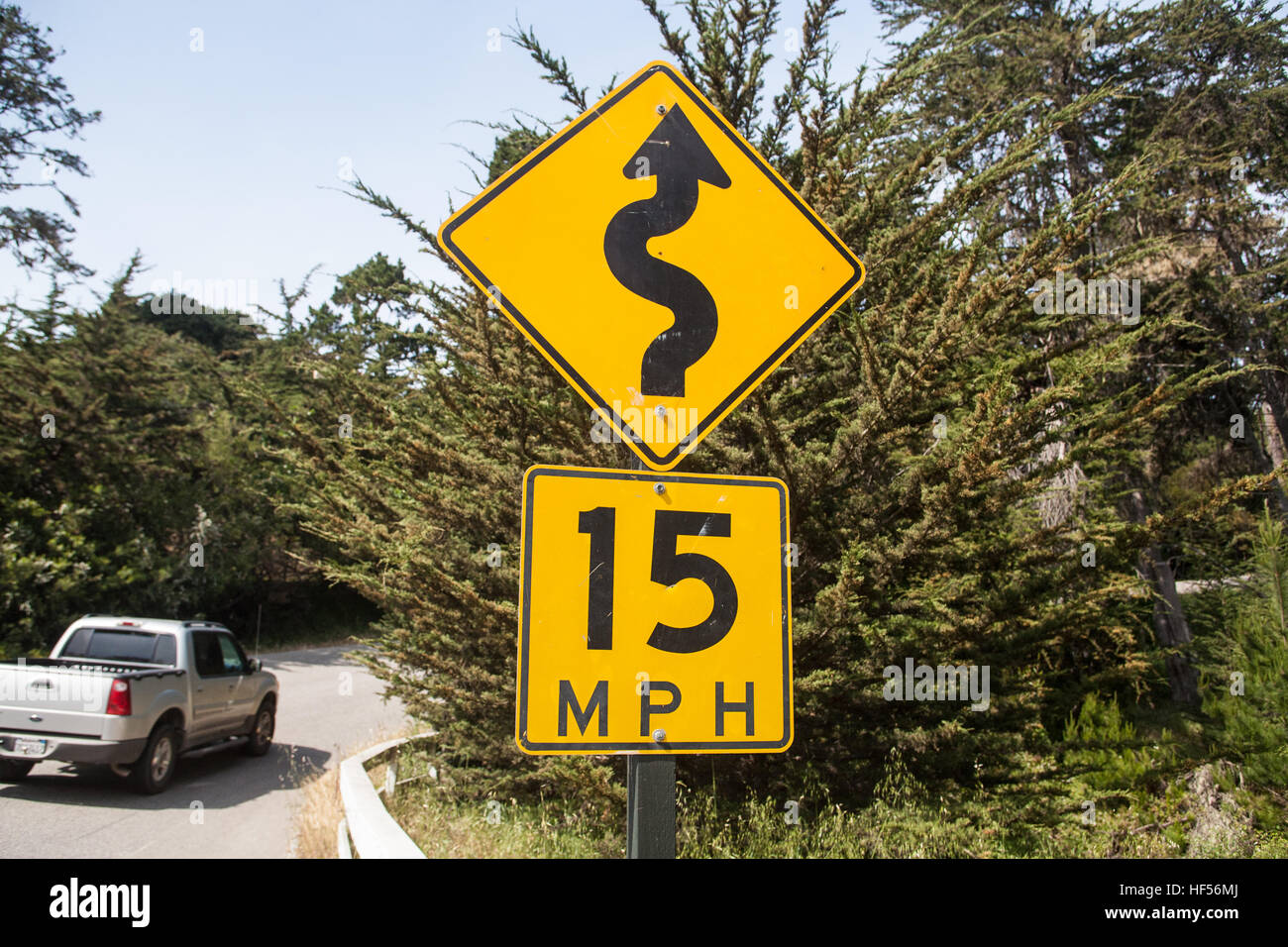 car,cars,on,Winding,bend,bendy,low,speed,limit,sign,on,road