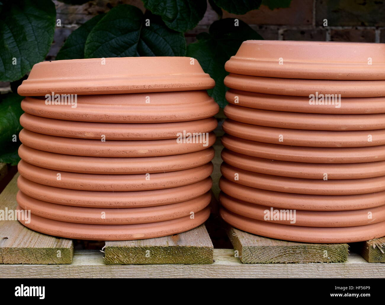 Stack of upturned terracotta garden saucers on wooden shelf - Stock Image