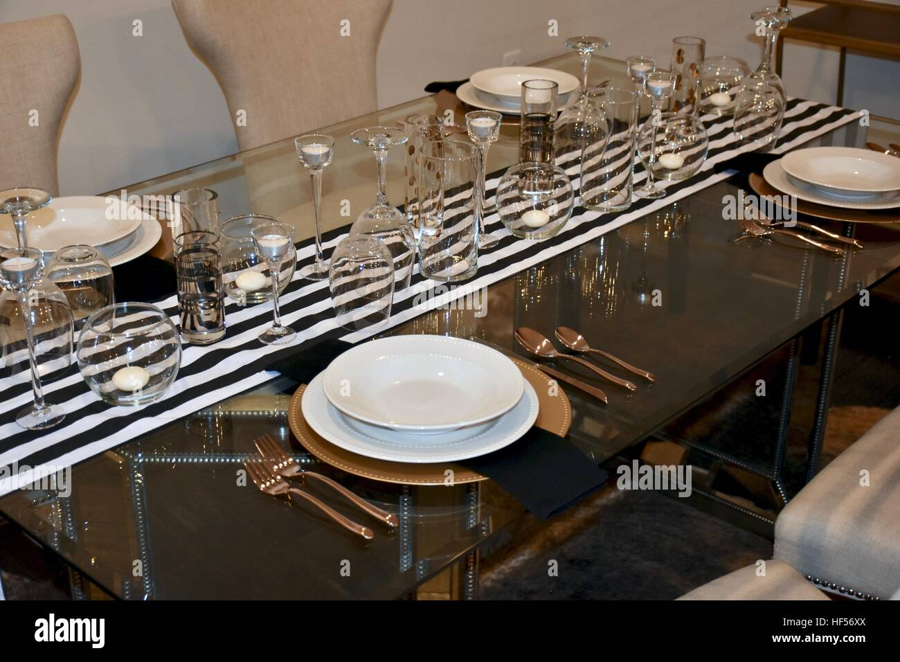 An elegant dinner set up prepared on a beautiful glass table for a ...