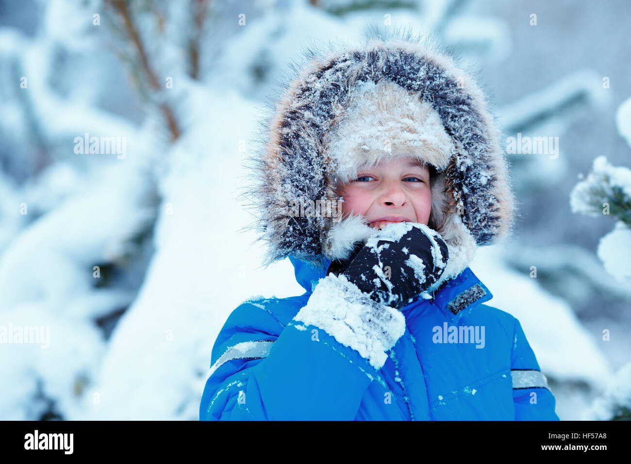 Portrait of cute kid boy trying to eat snow outdoors. Child having fun in a winter park - Stock Image