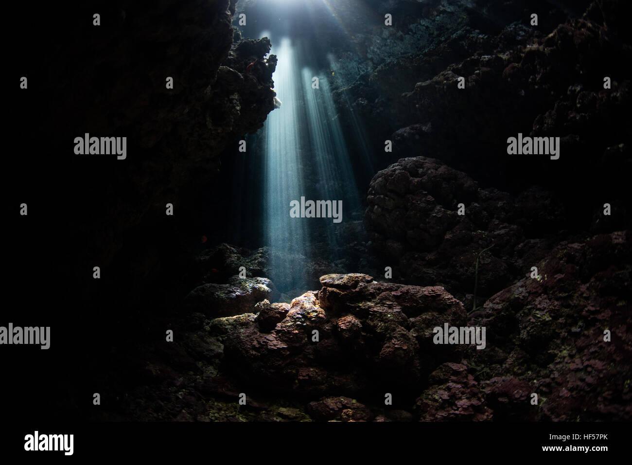 Beams of bright sunlight descend into a dark, underwater grotto in the Solomon Islands. This region harbors high - Stock Image