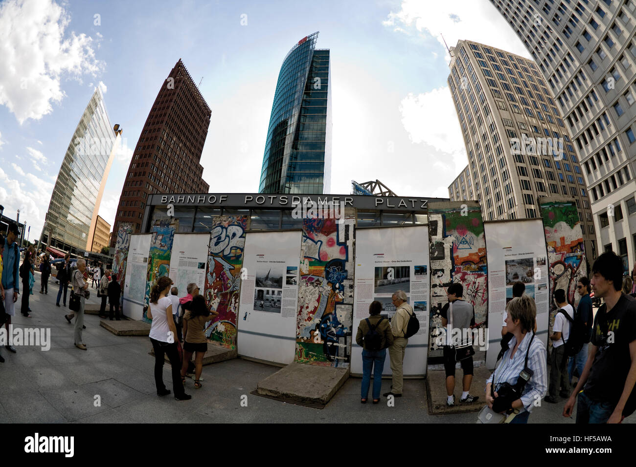 Tourists reading information about the Berlin Wall and the Sony Center and Bahntower (German Rail) building in the - Stock Image