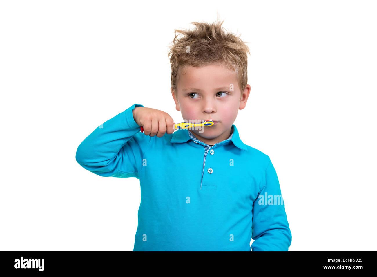 Little Boy Brushing Teeth on white background - Stock Image