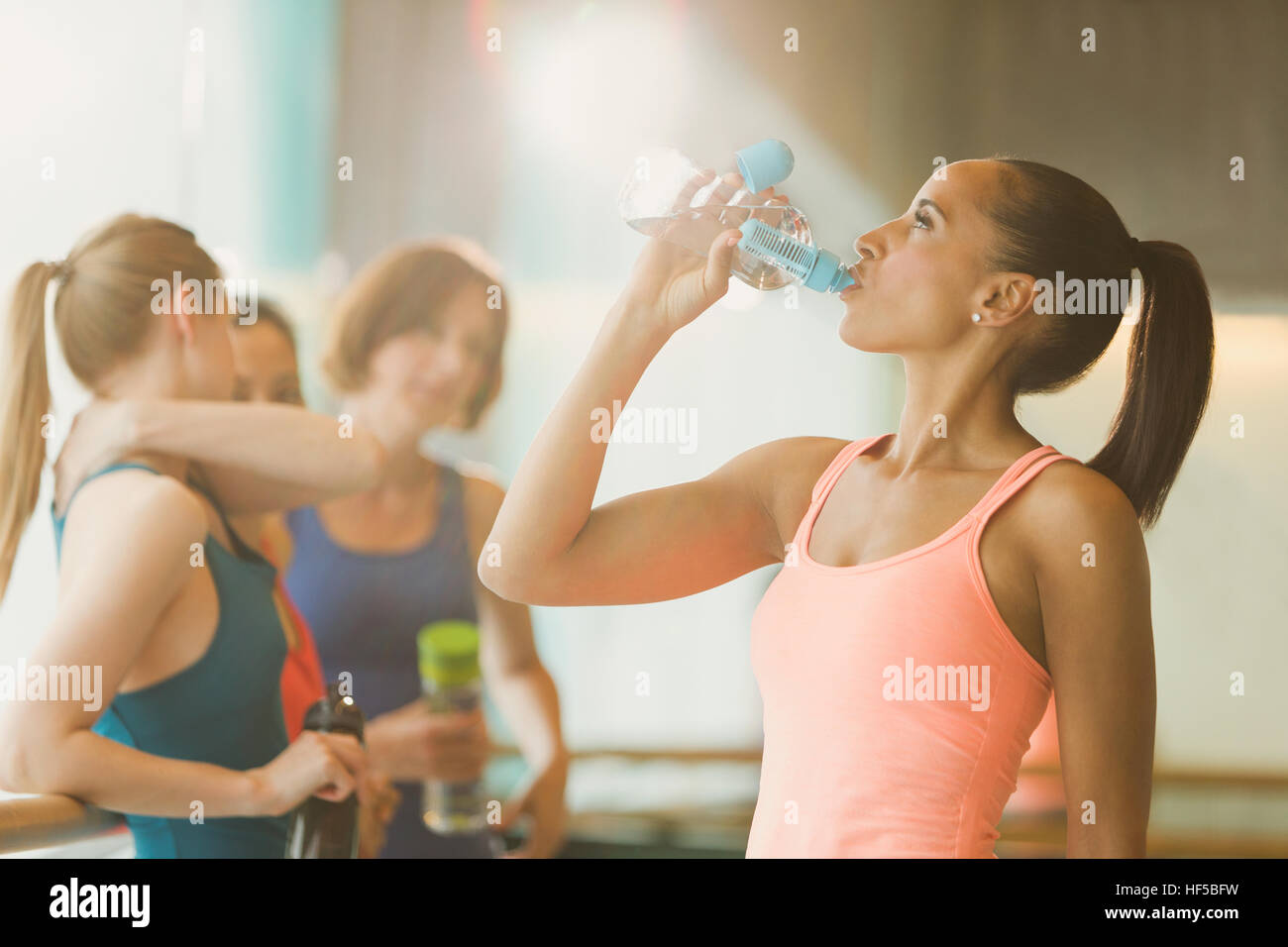 Woman drinking water in exercise class gym studio Stock Photo