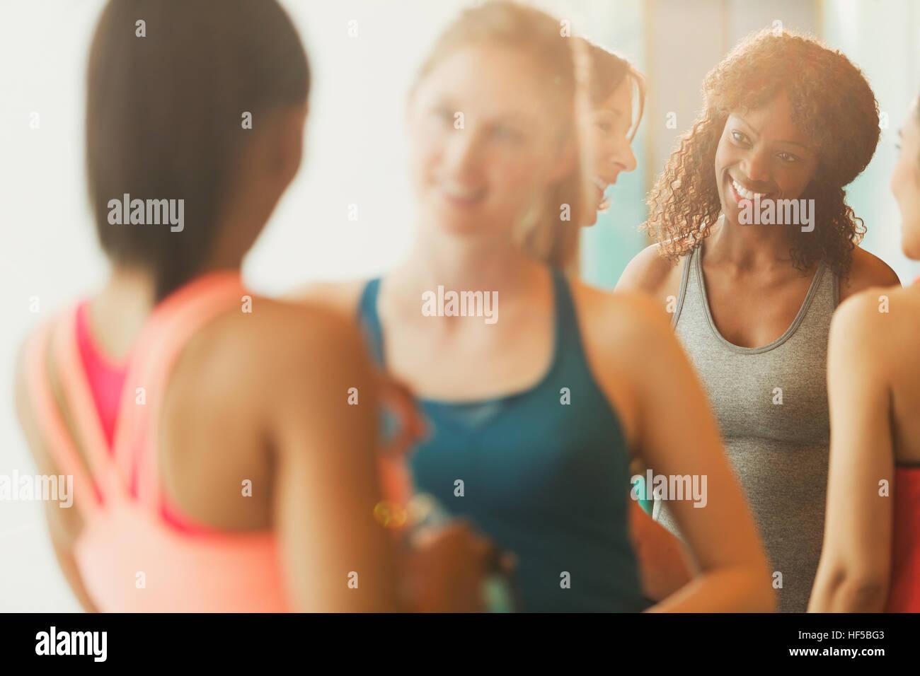 Smiling women talking in exercise class gym studio Stock Photo