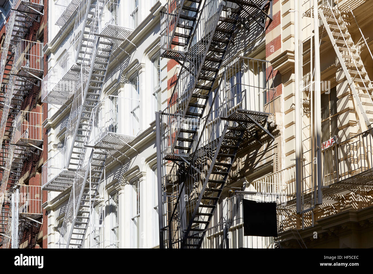 Houses facades with fire escape stairs, sunny day in Soho, New York background Stock Photo