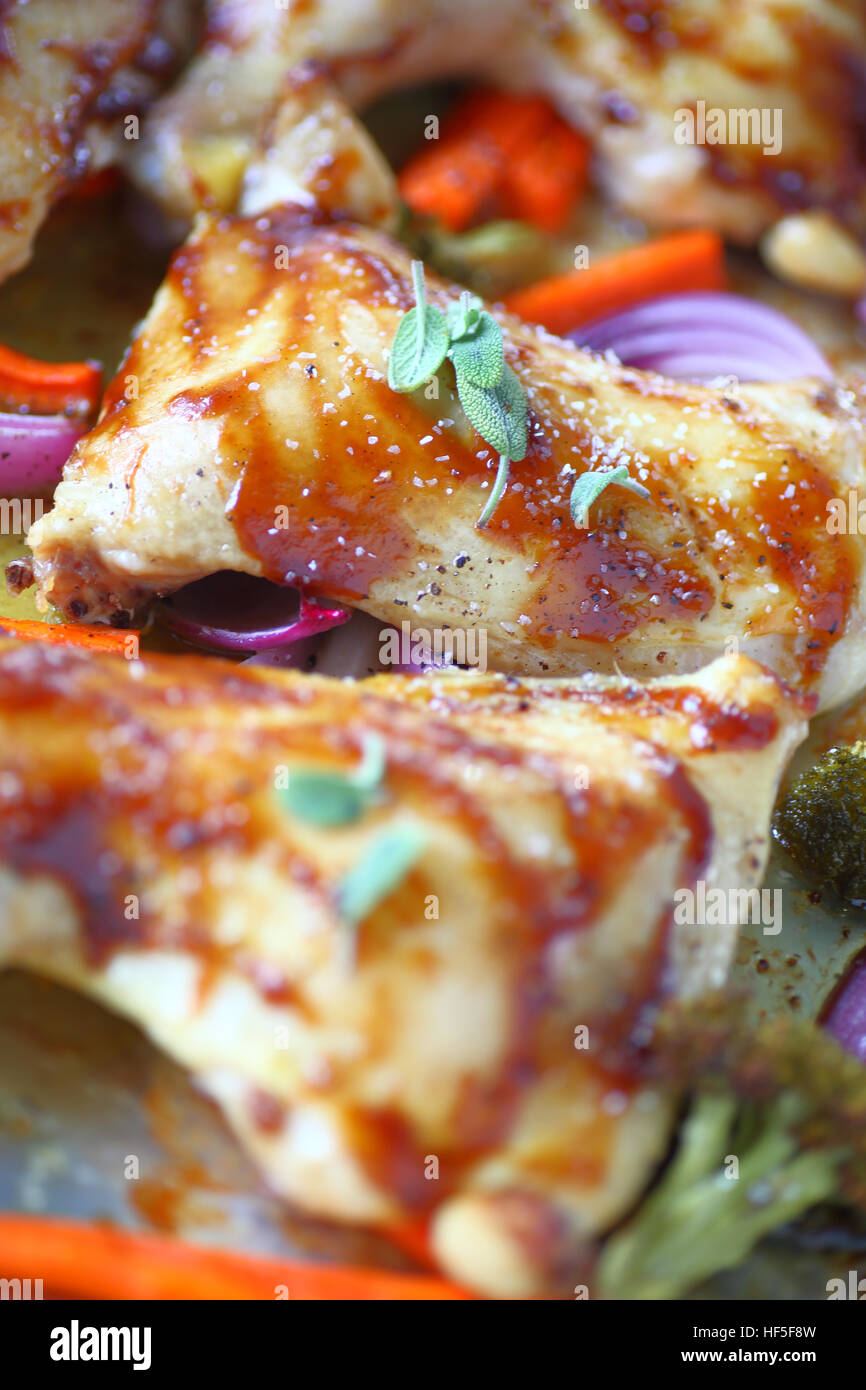 Chicken pieces roasted with hoisin sauce and coarse salt with onions, carrots and broccoli - Stock Image