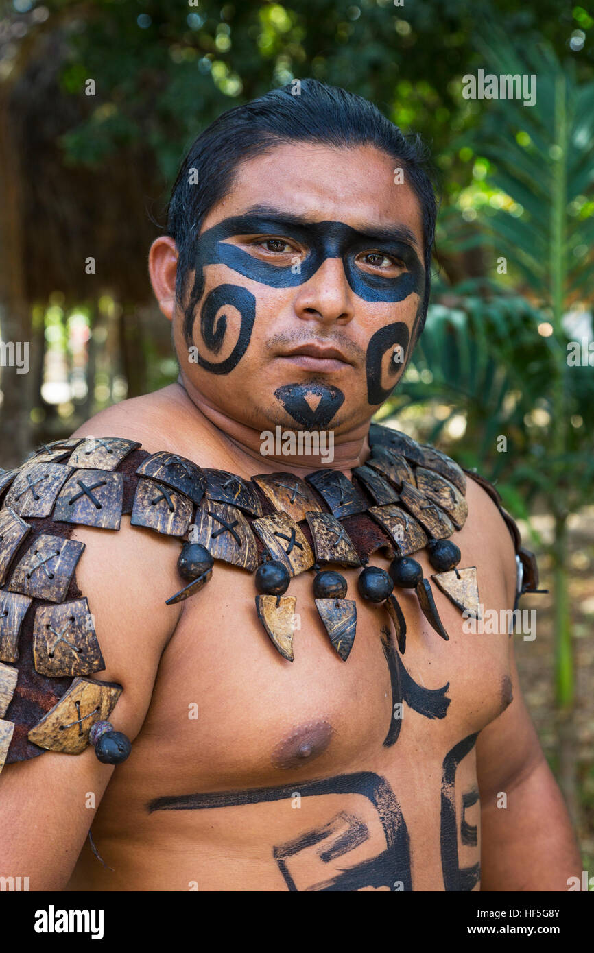 Local Mayan male dressed in the traditional face paint and body decorations of a Mayan warrior, Yucatan, Mexico - Stock Image