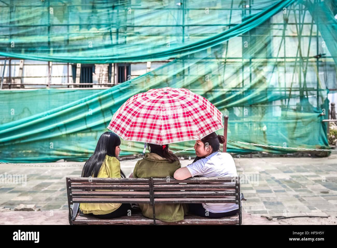 Three young women sharing an umbrella on a bright day in Hanuman Dhoka, Durbar Square, Kathmandu. © Reynold - Stock Image