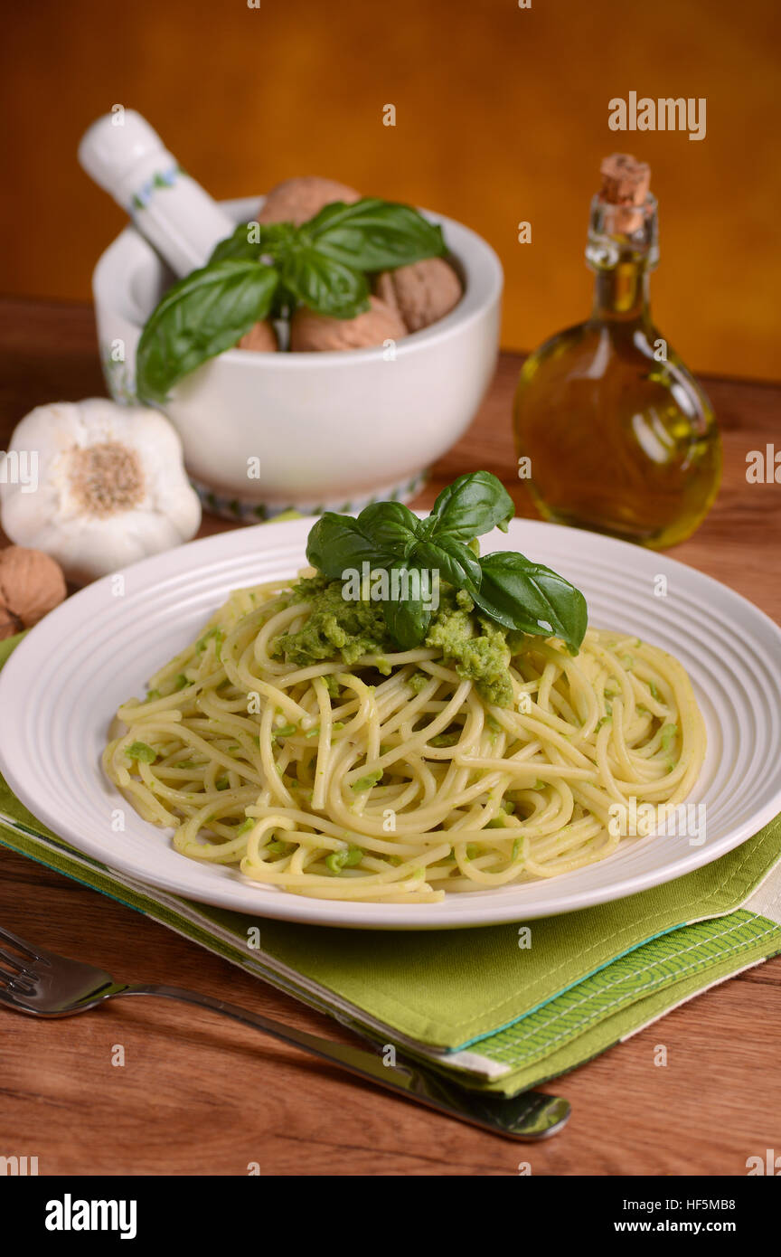 spaghetti with walnut pesto with ingredients around - Stock Image