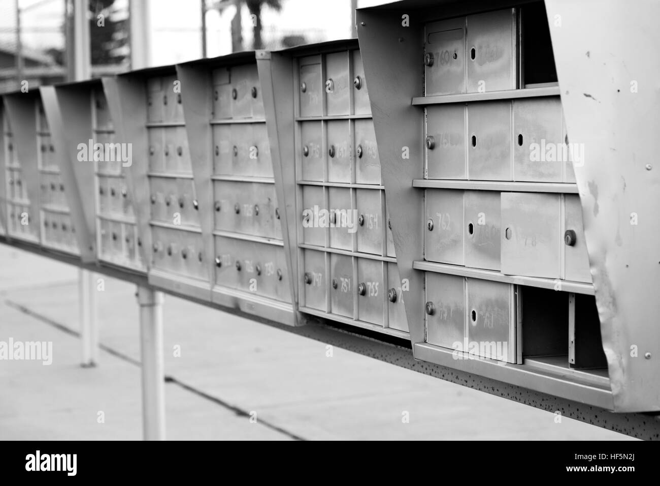 black & white photo of metal mailboxes lined in a row. Stock Photo