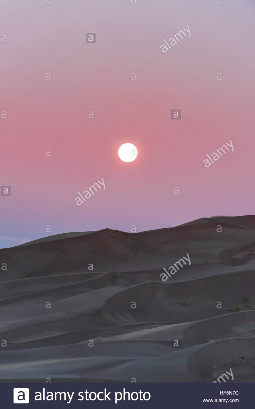 The full moon about to set over the 750 foot tall sand dunes, Great Sand Dunes National Park and Preserve, near - Stock Image