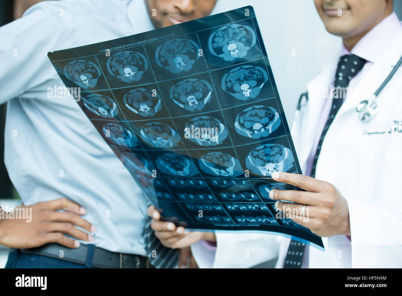 Closeup portrait of intellectual healthcare professionals with white labcoat, looking at full body x-ray radiographic - Stock Image