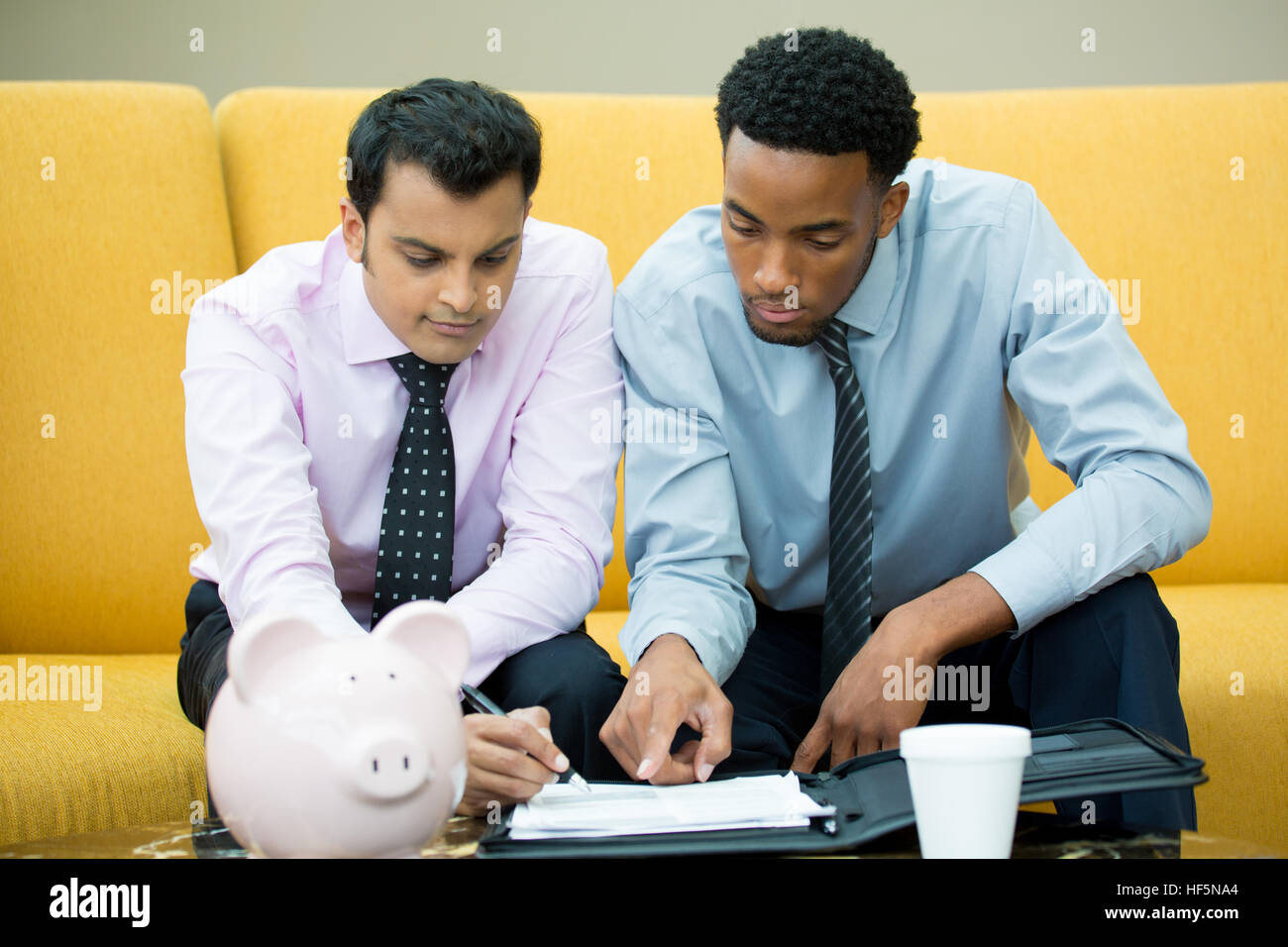 Closeup portrait, two young men in ties doing paper work for a contract isolated yellow couch background with piggy - Stock Image