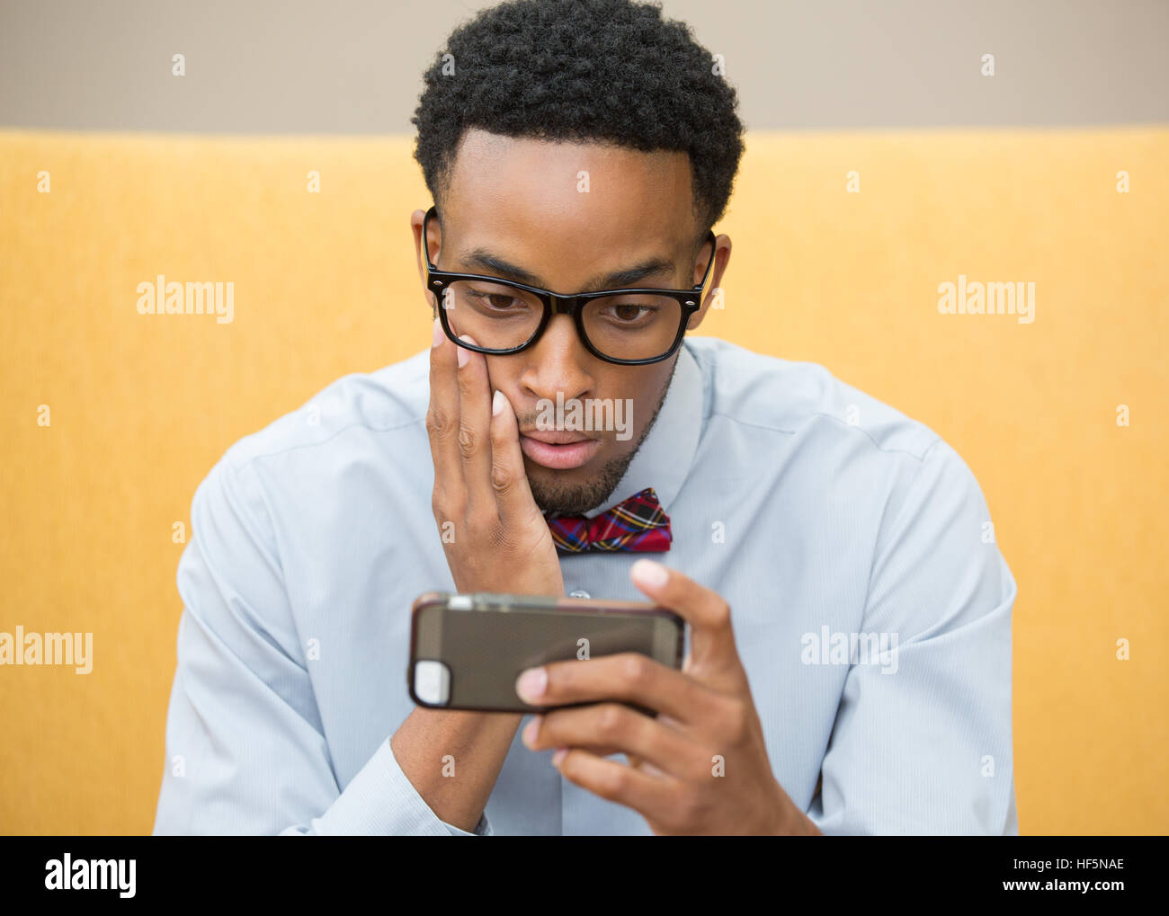 Closeup portrait stunned, surprised businessman in black glasses and bowtie, placing hand on cheek, staring at cellphone, - Stock Image