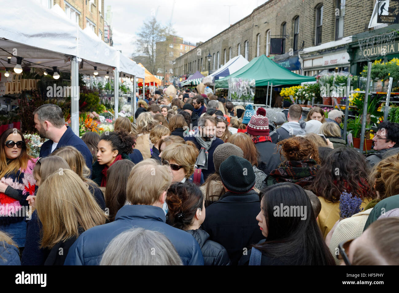 Crowds of people make Colombia Road flower market in East London a very congested place on Sunday mornings. - Stock Image