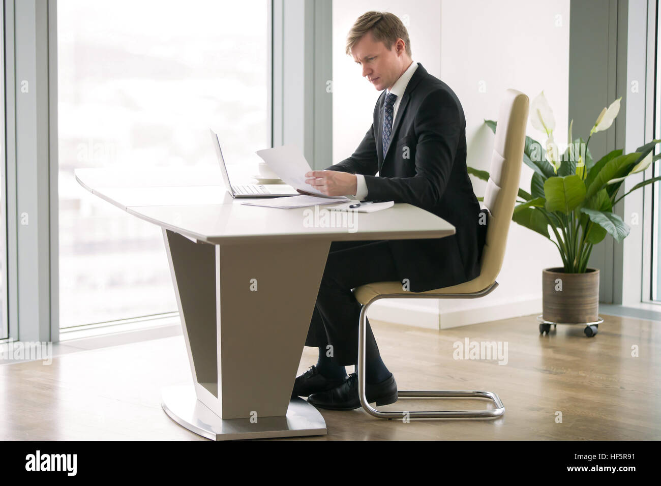 Businessman working with laptop and paper at the modern desk - Stock Image