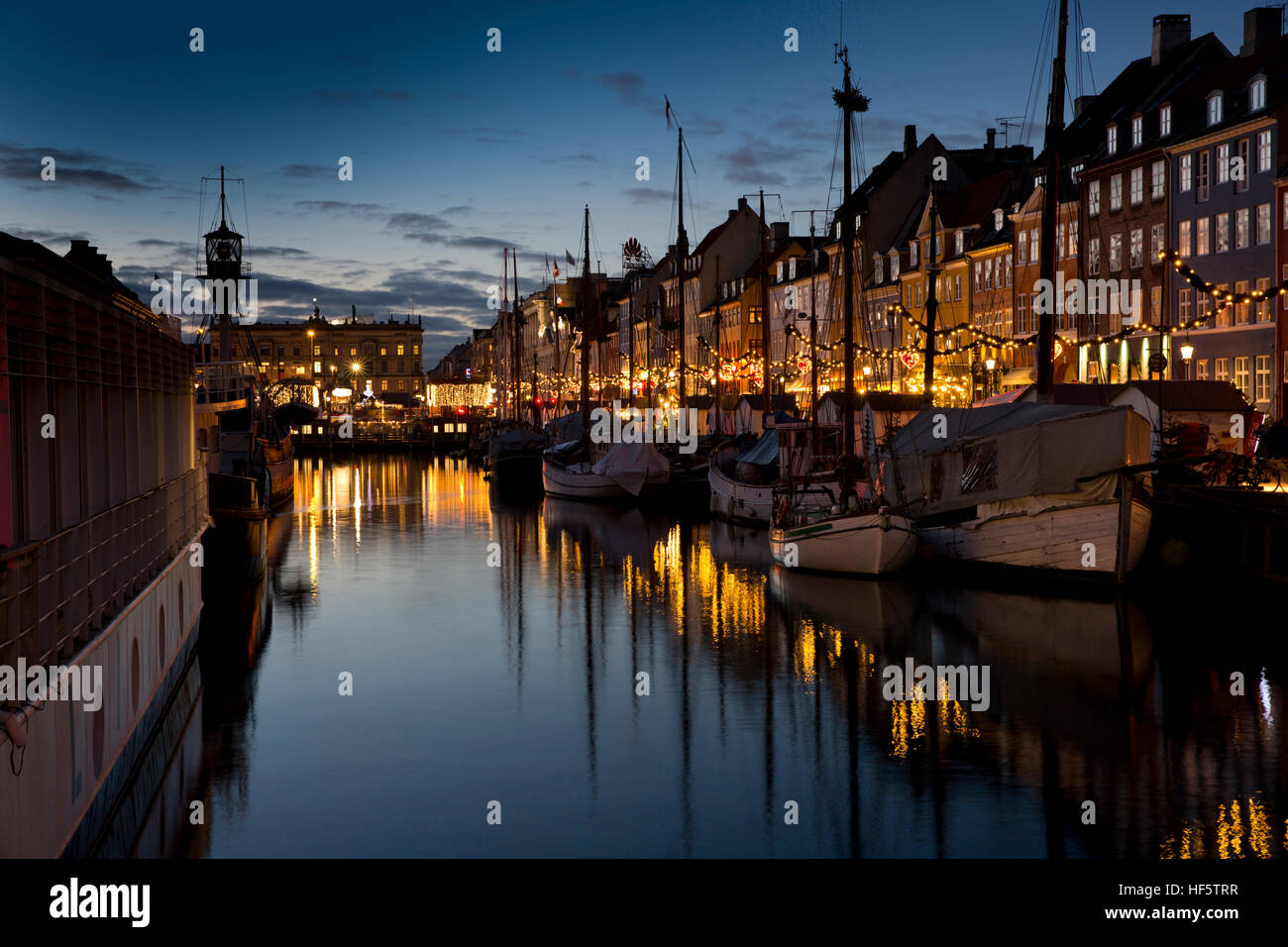 Denmark, Copenhagen, Nyhavn, winter, boats moored at quayside at night, reflected in water - Stock Image