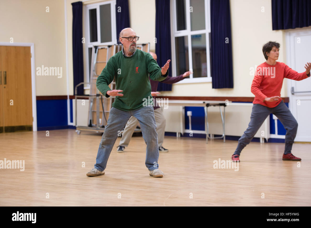 A group of middle aged people taking part in a Tai Chi class at Tregaron Memorial Hall, a small village hall modernised Stock Photo